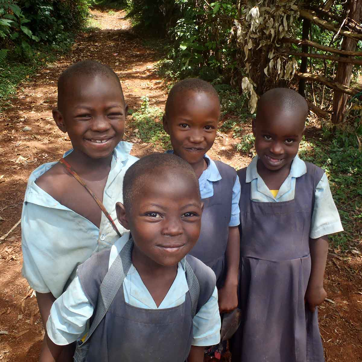Four smiling and precocious little Kenyan students posing on road to go to school.