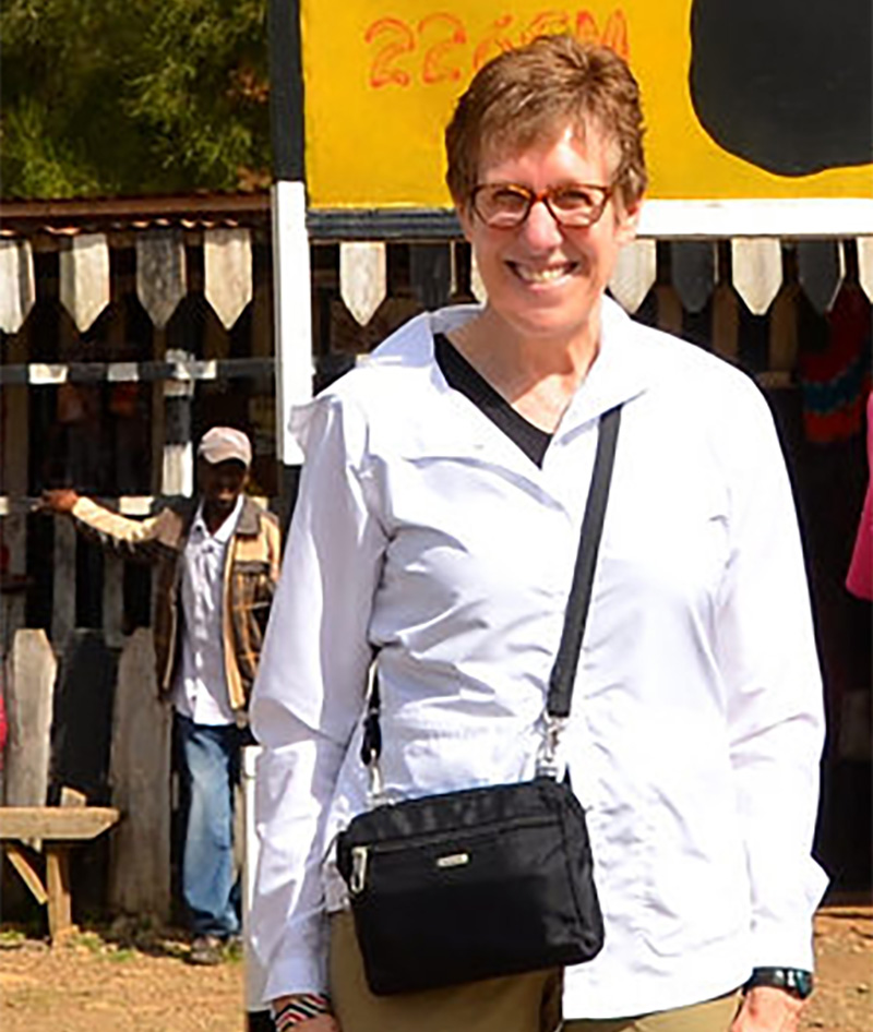 Beth Gaede standing near bright yellow sign in Kenya